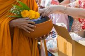 pic of buddhist  - Buddhist monk while stand in a row waiting people put rice offerings in their alms bowl for make merit  - JPG