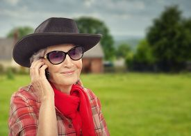 picture of cowgirl  - Joyful aged cowgirl is talking on smart phone - JPG