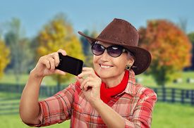 stock photo of cowgirls  - Aged cowgirl making selfie in front of ranch with smartphone - JPG