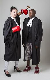 picture of toga  - woman hammering a man on the head with a gavel both wearing canadian lawyers toga - JPG