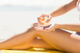 picture of sun tan lotion  - Close up view of Pretty blonde woman putting sun tan lotion on her hand at the beach - JPG