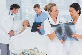 stock photo of x-files  - Doctors discussing about patients file in hospital room - JPG