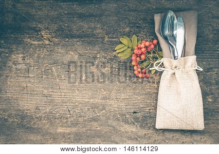 poster of Thanksgiving autumn place setting with cutlery on wooden background. Thanksgiving table setting cutlery on the autumn background. Thanksgiving holidays background concept. Copy space. Top view.