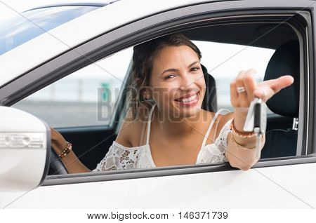 poster of Multiethnic woman showing new car keys and car. Young smiling girl driving her new car and looking a