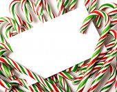 A white note-card, greeting card, or invitation surrounded by brightly color Christmas Candy Canes w