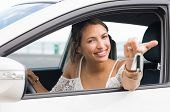 Multiethnic woman showing new car keys and car. Young smiling girl driving her new car and looking a poster