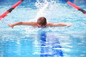 MOTION BLURRED IMAGE, SHALLOW FOCUS,  FOCUS ON WATER IN FRONT OF FACE, Boy swimming Butterfly in a r poster