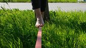 Woman Legs Walk Along A Tight Line In The Park. Foot Woman Balances On The Slackline Close Up. poster