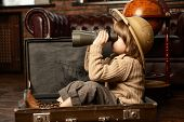 Cute child boy in a travel suitcase playing at home. Childhood. Fantasy, imagination.  poster