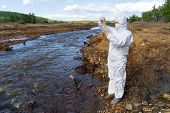 A Scientist In A White Protective Suit Takes Samples Of Water From A Polluted River. Concept - Pollu poster