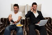 stock photo of video game controller  - Gamer and Businessman side by side on the couch - JPG