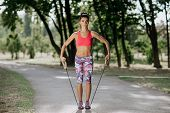 Female Athlete Exercising With Resistance Band In The Park. Tough Woman Using A Resistance Band In H poster