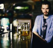 Service Concept. Guy Sits At Bar Counter With Beer. Glass Of Draft Beer On Blurred Bar Background. M poster