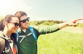 travel, hiking, backpacking, tourism and people concept - happy couple with backpacks walking outdoo poster