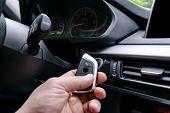 Closeup Inside Vehicle Of Man Hand Holding Wireless Key Ignition. Start Engine Key. Hand Holding Car poster