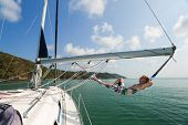 Young and happy sailor relaxes in a hammock set on the boom of the sailing boat anchored in a tropic poster