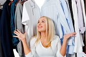 stock photo of wardrobe  - Overwhelmed woman picking clothes and sitting in a wardrobe - JPG