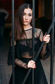 Portrait Of A Young, Beautiful Girl. The Brunette In A Black Dress Is Standing Near The Cage With Bl poster