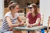 Joyful Female Companions In Shades, Have Friendly Talk In Coffee Shop While Wait For Order, Have Fun poster