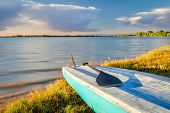 stand up paddleboard with a paddle on a lake shore in Colorado (Boyd Lake State Park), summer scener poster