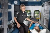 stock photo of triage  - Female EMT worker showing care to senior woman patient inside ambulance - JPG