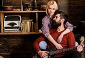 Lady And Man With Beard On Dreamy Faces Hugs And Plays Guitar. Couple In Wooden Vintage Interior Enj poster