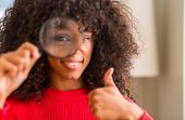 Curious african american woman looking through magnifying glass happy with big smile doing ok sign,  poster