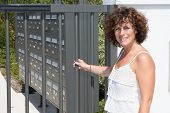 A Woman In Front Of The Mailboxes Of The Residence poster