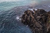 View From Above On  Lava Rocks And Turquoise Sea Covered With Ripples On Jeju Island poster