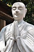 The Stone Statue Of Praying Buddhist Monk. Paying A Respect, Praying, Relax And Deep Meditation Conc poster