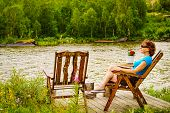 Mature Woman Enjoying Nature Landscape, Sitting On Chair On Lake Fjord Shore. Holidays Relaxation An poster