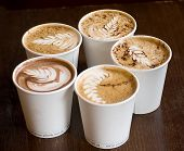 stock photo of frappe  - five cappuccino plastic cups over wooden table