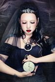 pic of freaky  - Young beautiful gothic woman holding clock in her hands - JPG