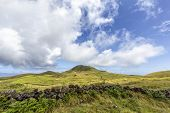 A Distant Volcanic Butte With Volcanic Rock Wall In Front Of Pastures On Pico Island In The Azores,  poster