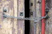 A Chain Of Silver Color With Closed Padlock On An Old Gate. Closeup Of Old Wooden Door With Closed P poster