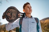 A Teenage Boy Holds A Skateboard In His Hands And Looks Away. Mountains And Sky In The Background. B poster