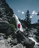 An Adventurous Guy Standing In Front Of A Huge Waterfall In The Yosemite Valley. People Who Adventur poster