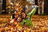 stock photo of throw up  - Kids playing in autumn park - JPG
