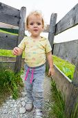 Cute Blonde Girl Walking Through Wooden Gate In Pasture Fence. poster