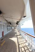 A Cruised Ship Promenade Deck With Teak Wooden Flooring And Hanging Safety Vessels poster