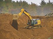 stock photo of power-shovel  - Excavator shovel digging in a mountain to level it - JPG