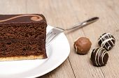 foto of tort  - Chocolade torte on a white plate with three chocolates - JPG
