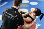 image of crunch  - Personal trainer helping young woman in gym with crunching exercises - JPG