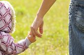 stock photo of mentoring  - parent holds the hand of a small child - JPG