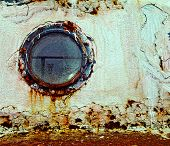 Rusty Porthole on the background of the old barge