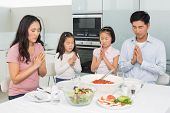 Family of four saying grace before meal in the kitchen at home