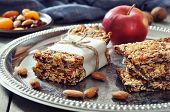 stock photo of roughage  - Granola bars on plate with nuts and dried fruits on wooden background - JPG