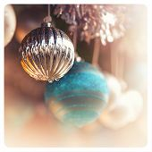 Detail of christmas baubles with tinsel. Selective focus and bokeh background. Cross-processed with