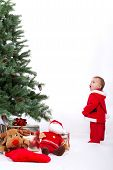 picture of fascinator  - Fascinated Santa Baby boy standing next to Christmas tree - JPG