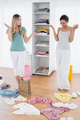 stock photo of scat  - Two happy young women looking down at shopping bag and scatted clothes on floor at home - JPG